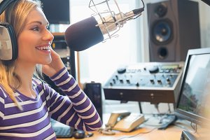 Happy female radio host broadcasting through microphone