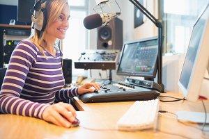Female radio host using computer while broadcasting