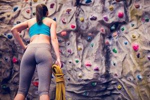 Fit woman looking up at rock climbing wall