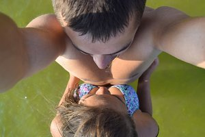 Man and woman doing selfie standing in the green sea water. Young girl hugging a guy
