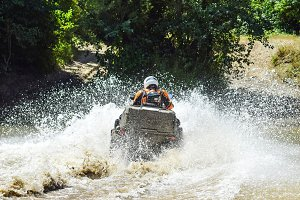 The man on the ATV crosses a stream. Tourist walks on a cross-country terrain