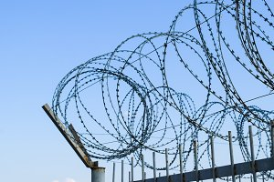 Barbed wire on the fence. Protective fencing specially protected object of barbed wire. Stamped barbed wire