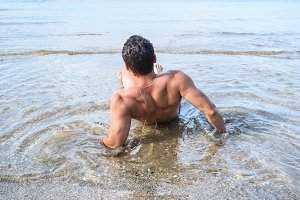The man on a sea beach. View from the back. A man gets out of the water