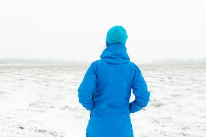 Woman in blue standing in a snowy field
