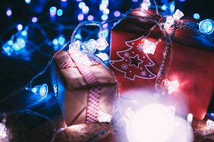 Christmas gift boxes with glowing garland and blue bokeh lights