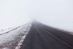 Snowstorm and poor visibility on the road, end is lost in the fog