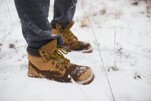 Closeup of male yellow winter shoes on snow