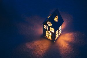 Lantern house with burning candle on snow in the evening