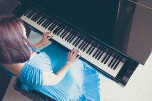 lady in blue dress playing a piano