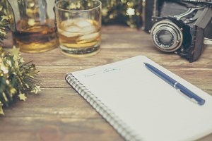 wooden background with notebook, pen and old camera