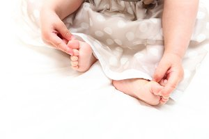 baby girl in the dress playing their feet