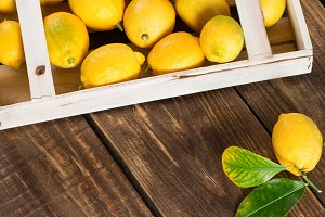 lemons with leaves in wooden crate