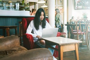 Asian girl using laptop in a cafe