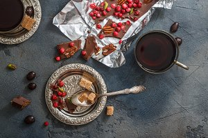 Chocolate bar with dry berries on silver vintage plate, close view, dark background