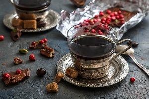 Vintage coffee cup, chocolate and cherries on the dark background