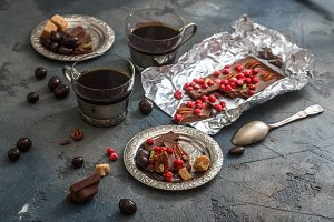 coffee in vintage silver cups on a dark background with chocolate. Close view