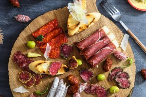 Different spanish embutidos on a table: jamon, chorizo, salami, cheese and wine. Top view