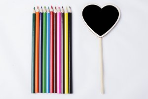 Wooden pencils next to small blackboard with heart shape on white background.
