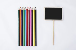 Wooden pencils next to small square blackboard on white background.
