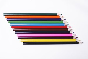 Wooden pencils of various colors on white background.