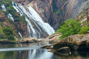 Mountain waterfall and summer river.