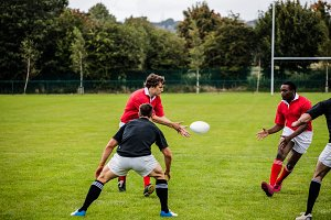 Rugby players passing during game