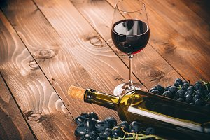 Bottle of white wine, grapBottle and glass of red wine, grape and cork on wooden background e and corks on wooden table