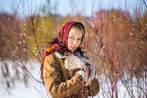 Fashion outdoor portrait of beautiful blonde woman clothed in scarf and sheepskin coat among blooming willow willows. Russian national winter clothes.