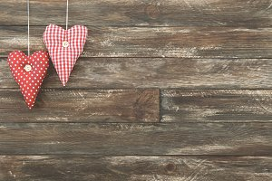 Vintage Red Hearts Hanging over Brown Wooden Background