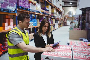 Warehouse manager and worker looking at tablet
