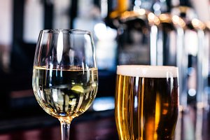 Close up of a glass of wine and a beer