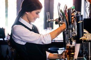 Barmaid serving a pint