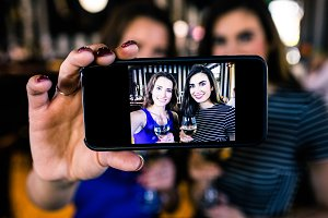 Happy brunettes taking selfie with white wine