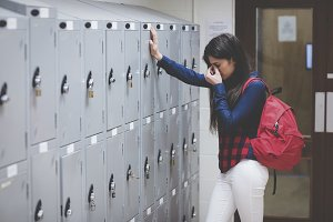 Stressed student beside her locker