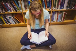 Blonde student reading while sitting on books