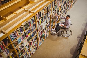 Student in wheelchair picking a book from shelf