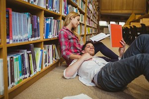 Student reading book while lying on his classmate