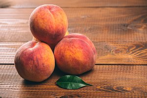 Fresh beautiful fruit peaches on wooden background
