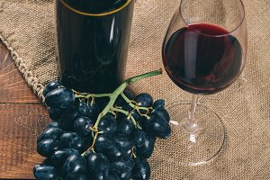 Bottle and glass of red wine and grape on wooden background with burlap