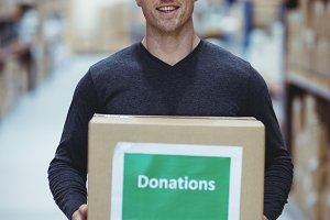 Volunteer smiling at camera holding donations box