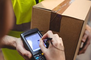 Woman signing on device to delivery parcel