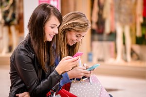 Two beautiful women using their phone in shopping mall