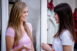 Two beautiful women talking outside a shop