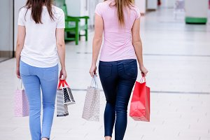 Rear view of women walking in mall with shopping bags