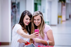 Two beautiful women taking a selfie in shopping mall