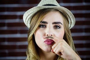 Pretty blonde woman doing a moustache with her finger
