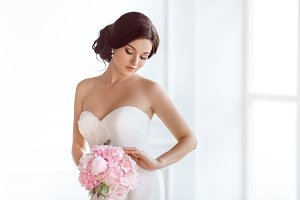 Beautiful bride. Wedding hairstyle make-up luxury fashion dress and bouquet of flowers.