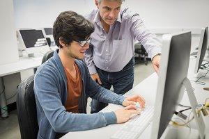 Computer teacher assisting a student