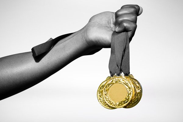 Hand holding three gold medals