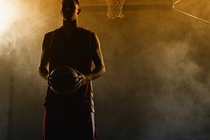 Portrait of a basketball player holding a ball in his hands